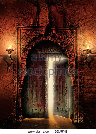 Ornate, ancient doorway with door partly open - Stock Image