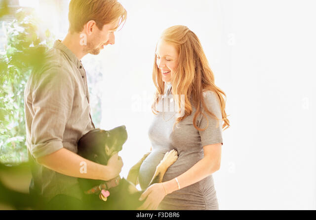 Mid-adult couple playing with dog - Stock Image