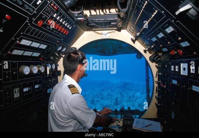 Underwater Atlantis submarine pilot at controls looking through viewport porthole window - Stock Image
