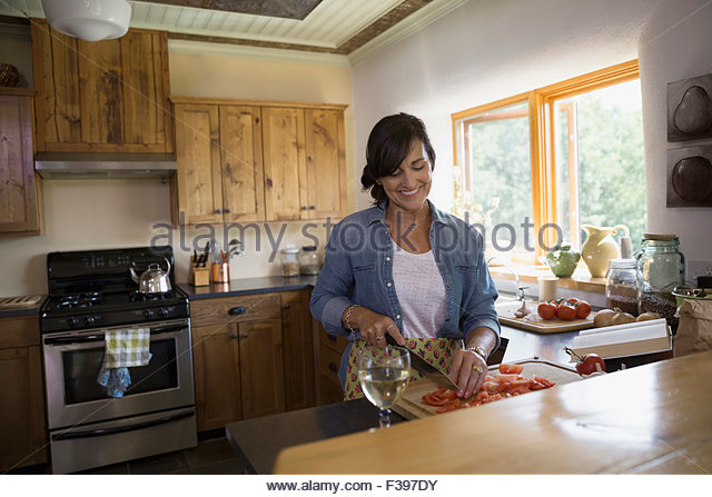 Woman drinking wine and cutting tomatoes in kitchen - Stock Image