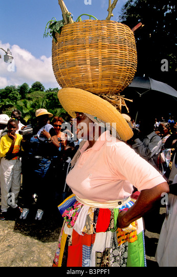 Caribbean woman wears straw basket on her head at the Tobago Heritage Festival an annual  Caribbean cultural celebration - Stock Image