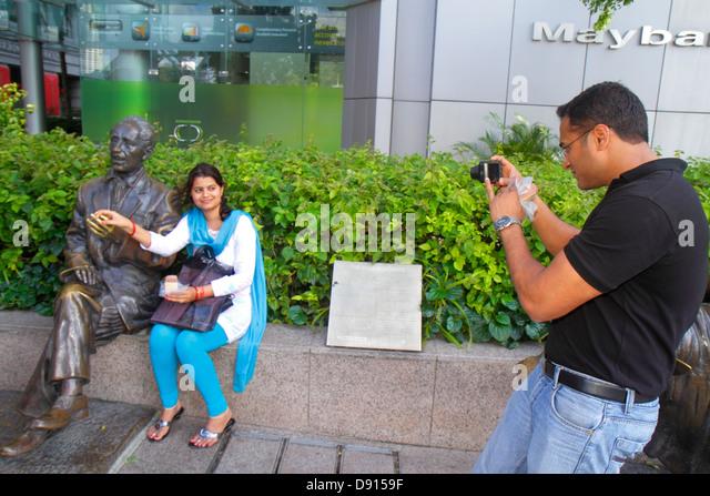 Singapore Singapore River Boat Quay Asian man woman couple taking picture camera life-size bronze statue - Stock Image