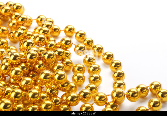 Golden color beads on white background. - Stock Image