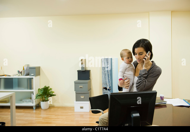 Mother holding baby while taking phone call in office - Stock Image