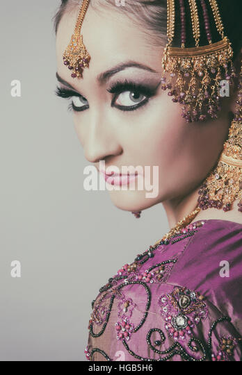 Serious Asian bride looking over shoulder - Stock Image