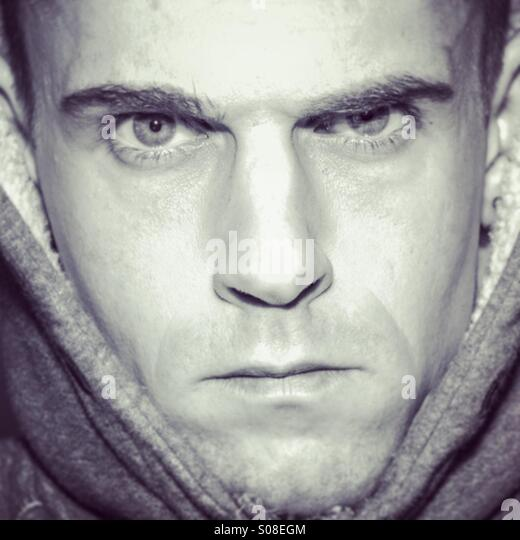 Unhappy moody male portrait, face filling the frame - Stock Image