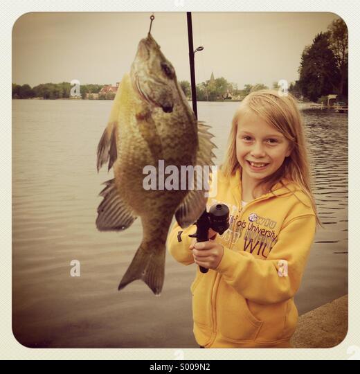 A little girl reels in a little fish. - Stock-Bilder