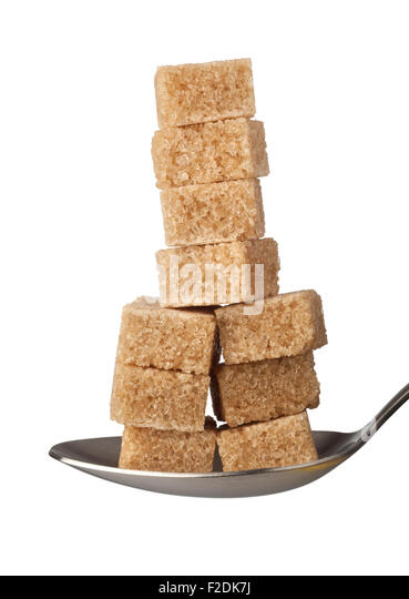 Stack of brown sugar cubes on a spoon isolated on white background - Stock Image