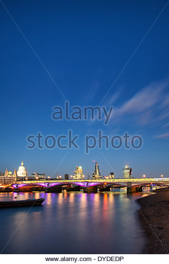 View along River Thames at night of London city skyline. - Stock Image