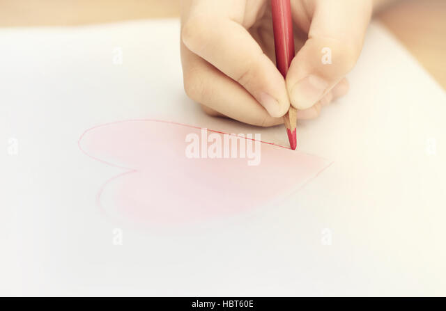 Child is drawing red heart - Stock Image