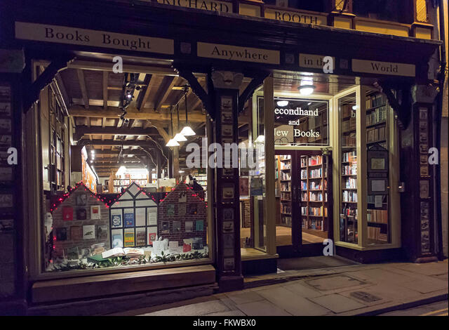 A bookshop lit at night in Hay on Wye, Colour, color, horizontal - Stock Image