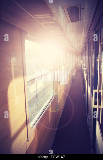 Retro filtered picture of a train coach interior with flare effect. - Stock Image