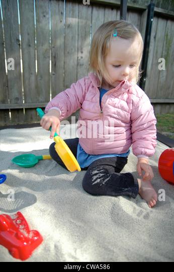 Little Girl Playing In Sandbox - Stock Image