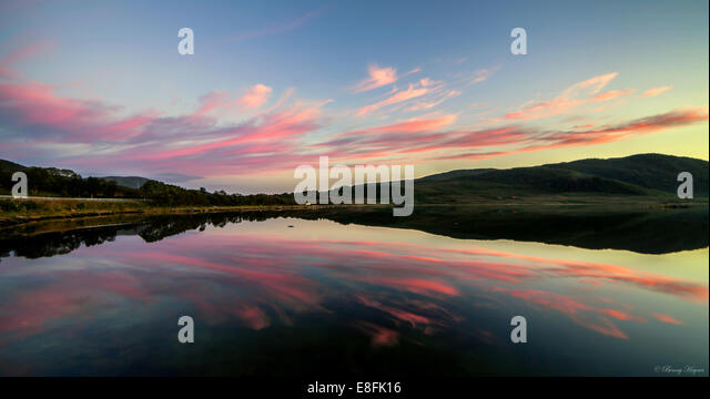 Norway, Roksa, Evening with calm water and pink clouds - Stock Image