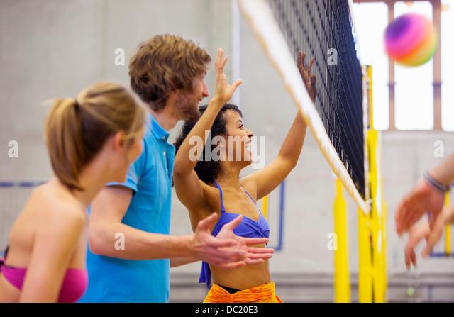 Friends enjoying indoor beach volleyball - Stock Image