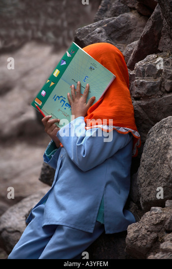 Muslim girl hiding her face with a book - Stock Image