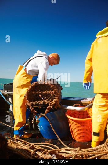 Fishermen at work on boat - Stock Image