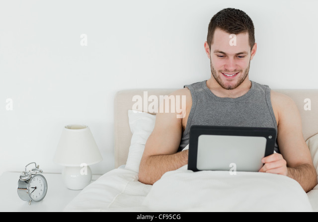 Peaceful man using a tablet computer - Stock Image