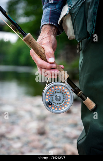 Man with fly fishing rod and reel, close up - Stock Image
