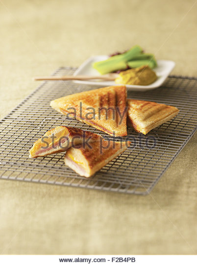 Grill ham and cheese pocket sandwiches with honey mustard and celery stick - Stock Image