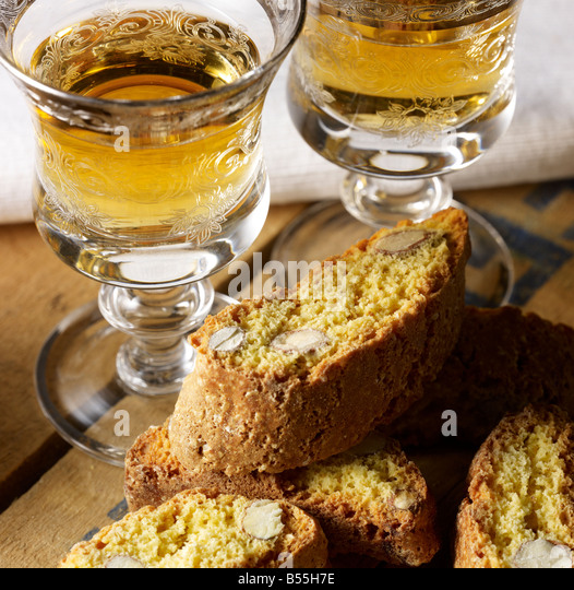 Two wine glasses filled with Vin Santo with Italian almond biscuits - Stock Image
