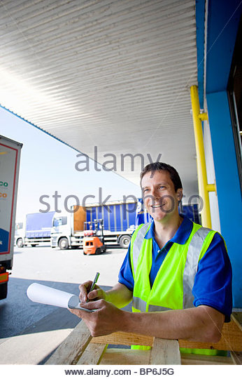 Worker writing on clipboard on loading dock - Stock Image