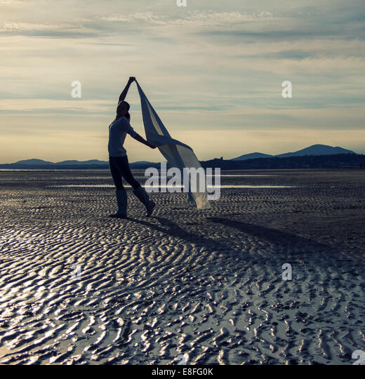 Woman standing on beach holding scarf - Stock Image