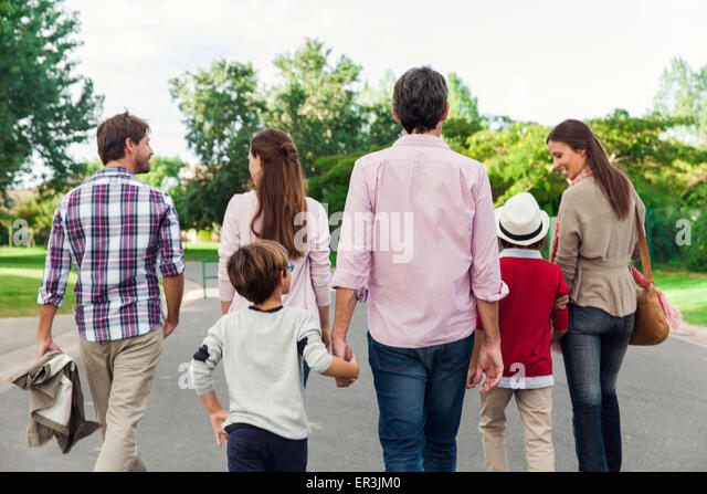 Family walking together outdoors, rear view - Stock-Bilder