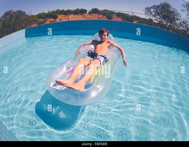 High Angle View Of Boy On Pool Raft Over Swimming Pool - Stock Image