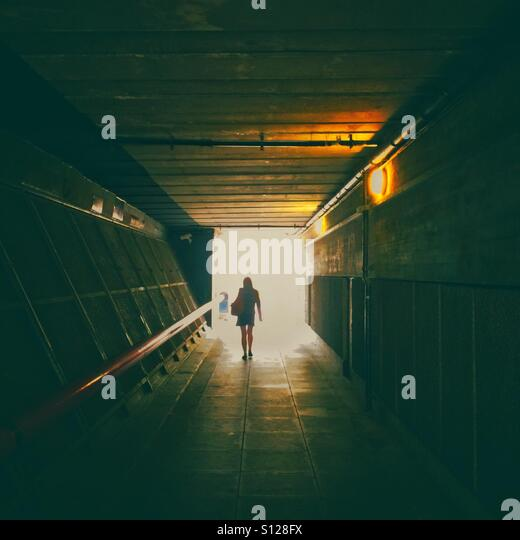 A woman walking in a tunnel - Stock Image