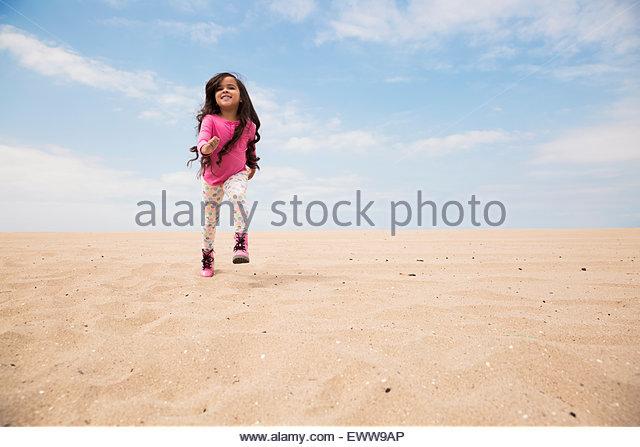 Smiling girl long hair running on beach slope - Stock Image