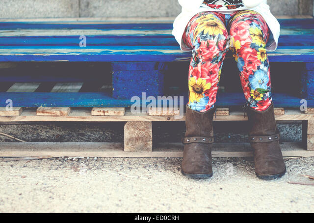 Low-section of girl (6-7) sitting on pallet - Stock Image