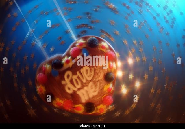 Love heart made of honey cake swinging on a broken string in circulating stars - Stock Image