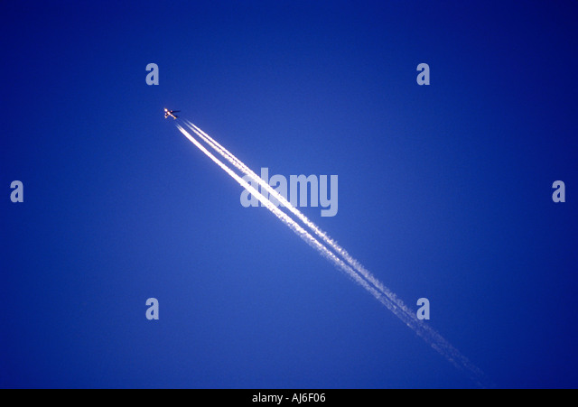 Commercial passenger airliner and vapor trail in sky - Stock Image