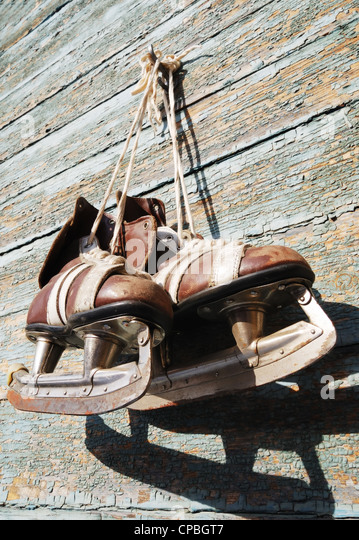 vintage pair of mens ice skates hanging on a wooden wall - Stock Image