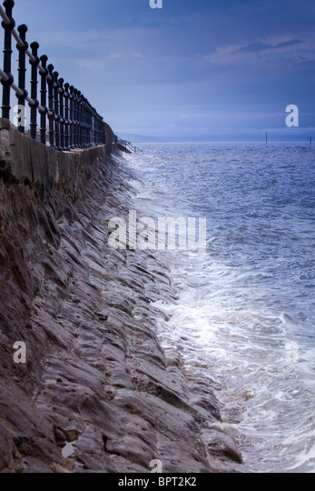 The sea and waves up against a sea wall on the coast in the Wirral, England - Stock Image
