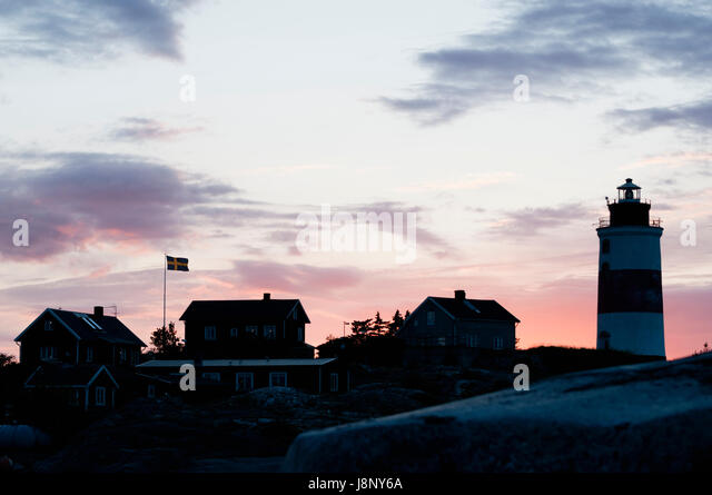 Small houses and lighthouse by sea at sunset - Stock-Bilder