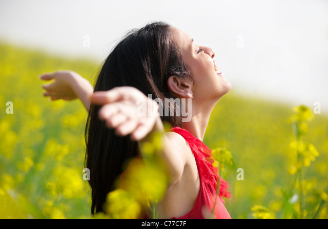 Young woman enjoying herself in a field - Stock-Bilder