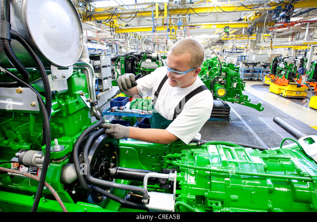 Worker is connecting hoses between the engine and the gearbox in the engine assembly area of the tractor production - Stock Image