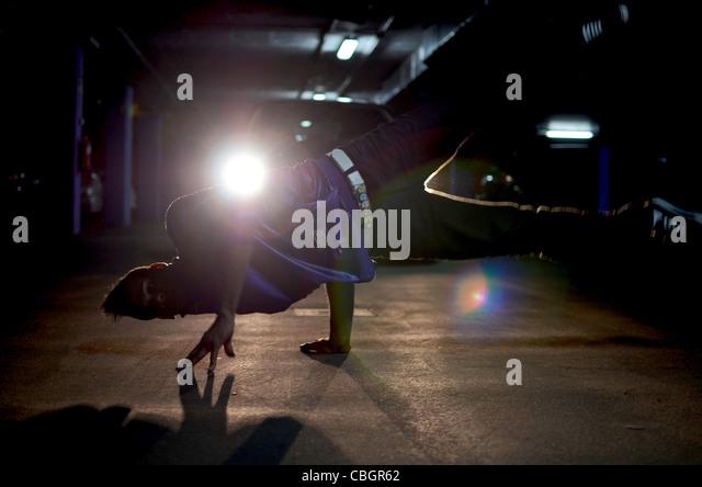 Breakdancer John Lartey performs in a garage - Stock Image