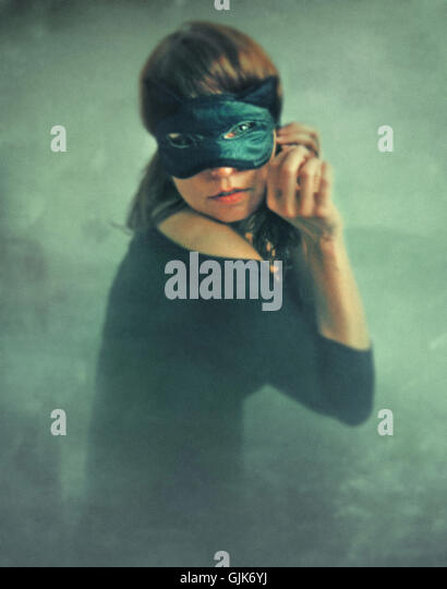mysterious young woman wearing black cat mask on her face - Stock-Bilder
