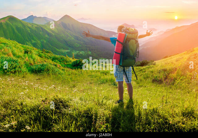 Hiker with a backpack standing in mountains. Amazing nature landscape. Soft light effect - Stock Image