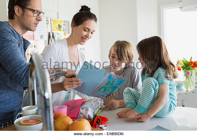 Family watching mother read homemade Mothers Day card - Stock Image
