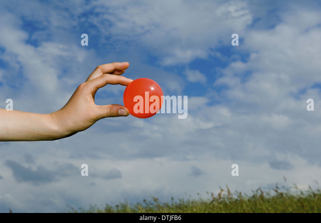 A person's outstretched hand holding a red ball Gloucestershire England - Stock Image
