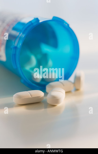 Close up of pills spilling out of bottle - Stock Image