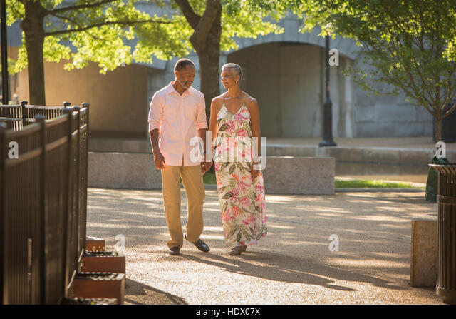Black couple holding hands walking in park - Stock Image