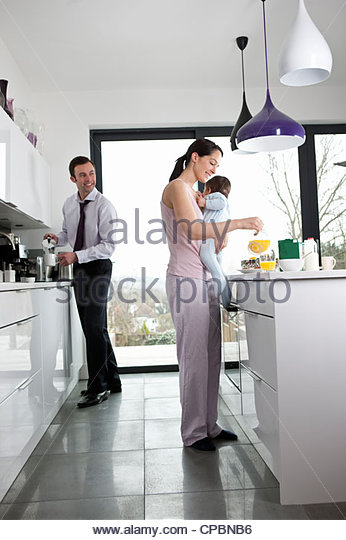 A couple and their baby son in the kitchen making breakfast - Stock-Bilder