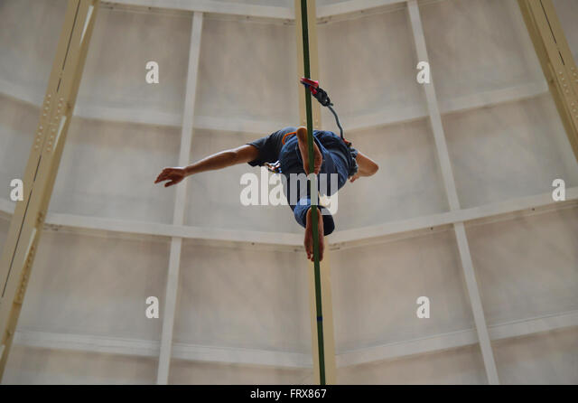 Tightrope walker at the top of the Devonshire Dome in Buxton, Derbyshire. - Stock Image