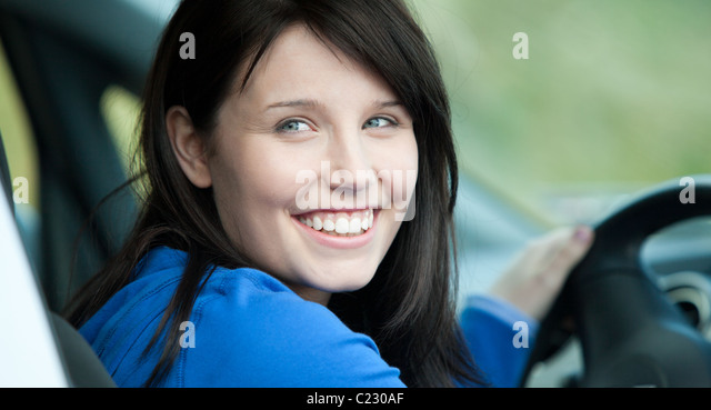 Bright female driver sitting in a car - Stock Image