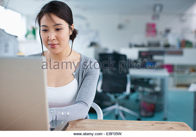 Smiling businesswoman working at laptop in office - Stock Image